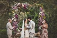 Noiva olhando noivo em frente a um arco de flores da decoração de casamento estilo boho RJ