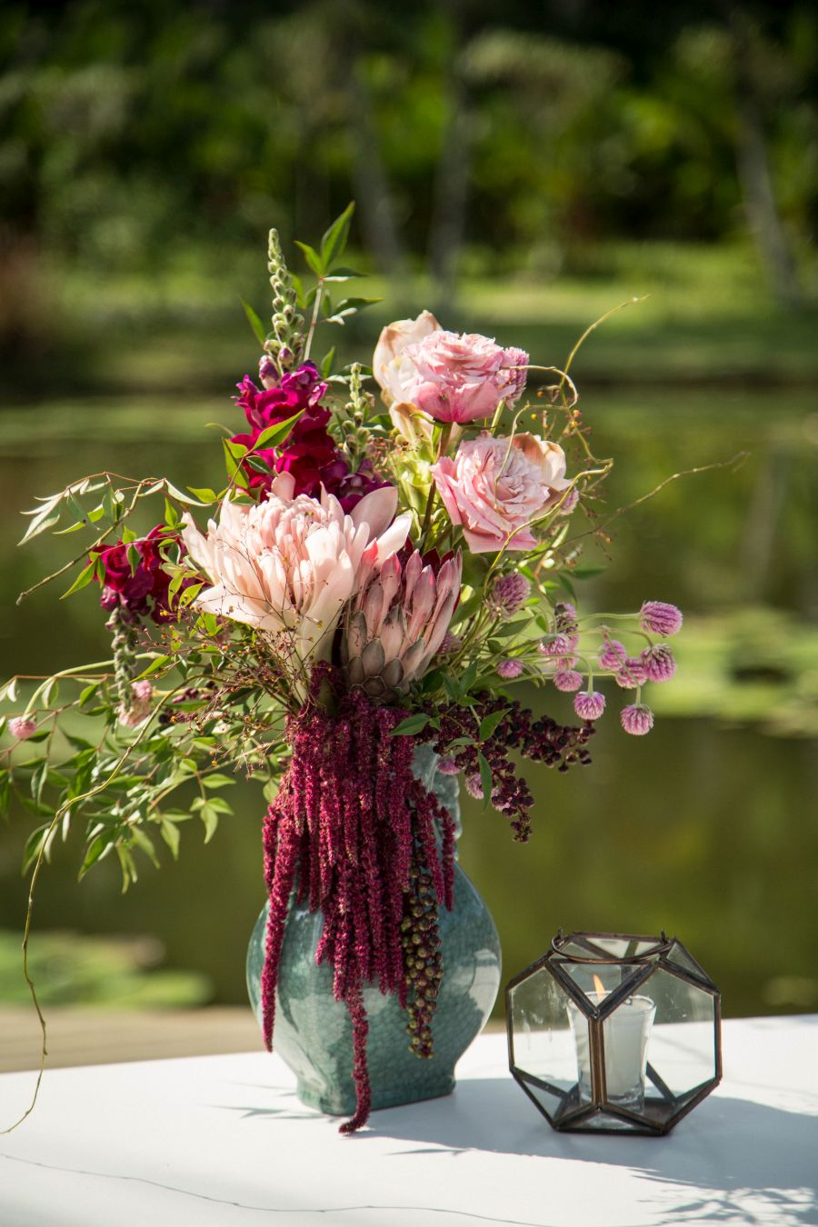 Decoração de casamento ao ar livre no RJ | Vaso de flores ao lado de vela decorativa, sobre mesa ao lado do lago.