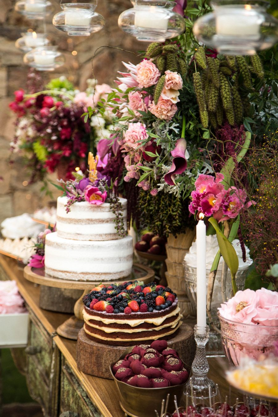 Decoração de casamento ao ar livre no RJ | Mesa de doces decorada com flores, e velas penduradas.