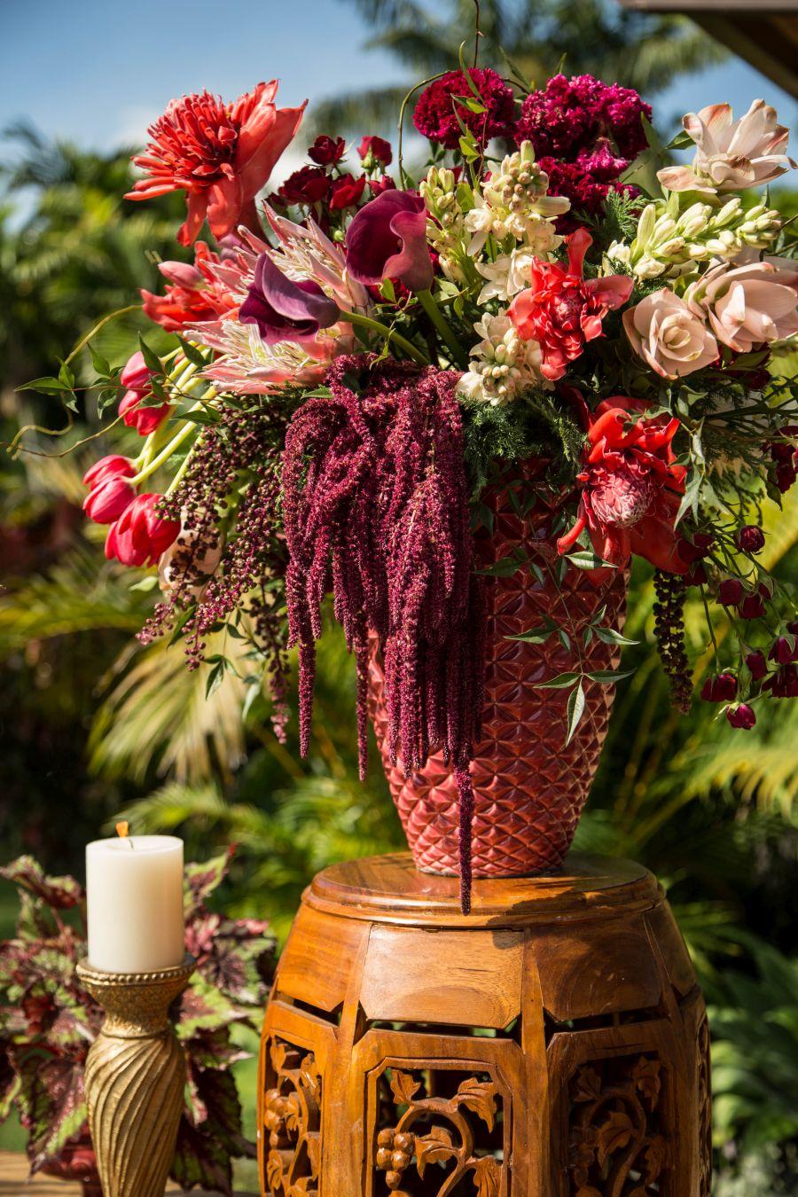 Decoração de casamento ao ar livre no RJ | Vaso de flores variadas, sobre aparador exposto ao ar livre no jardim, ao lado de vela decorativa.